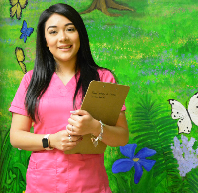 Febres Dentistry employee wearing pink scrubs and holding clipboard while in front of wall with grassy artwork.