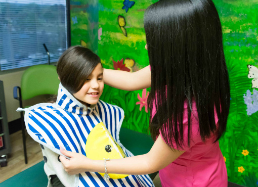 Febres Dentistry employee putting x-ray apron on girl.
