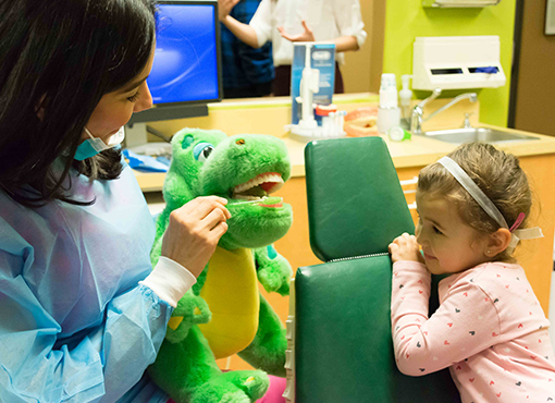 Febres Dentistry employee showing how to brush teeth by using a tooth brush on a dinosaur doll to small girl.